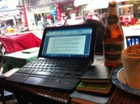 Today's office: A laptop, three notebooks, a coconut, and a celebratory beer after the first 2,000 words.