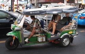 A tuktuk zooms through the streets of Bangkok.