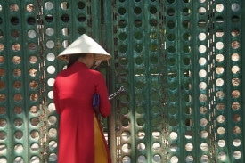 A tour guide opens the gate of a torturous, former political prison gate on Côn Sơn Island