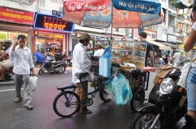 A bicycle street food vendor on Bui Vien Street.