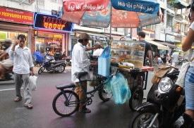 A bicycle street food vendor on Bui Vien Street.