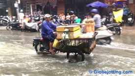 A motorbike with fresh coconuts for sale splashes through flooded Bùi Viện Street.