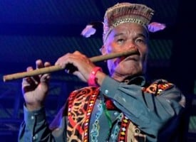 71-year-old Juk Wan Emang rocks out on the Sarawak nose flute, an instrument traditionally used by Borneo's Kayan people in courtship rituals. Copyright Dave Fox / Globejotting.com