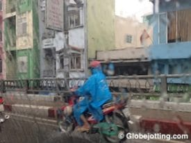 Motorbikes are the vehicle of choice in Saigon. In heavy rain, traffic thins out, but many people put on ponchos and keep going.